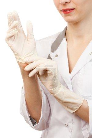Nurse putting on sterile gloves