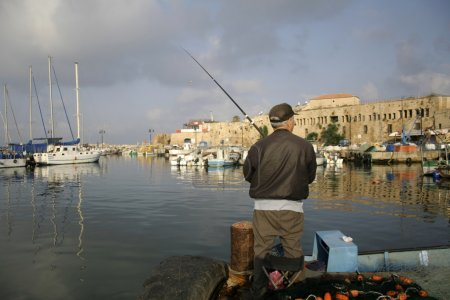 Rod fisherman in akko harbour israel