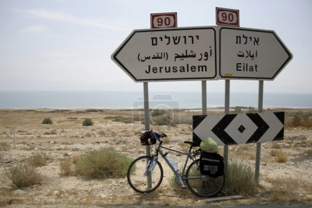 Bicycle parked against the jerusalem and eilat road signs