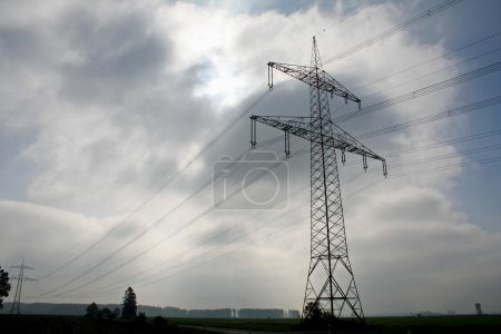 Electric lines on a dark cloudy sky