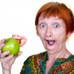 Elderly lady losing her teeth on a bite of an appl...