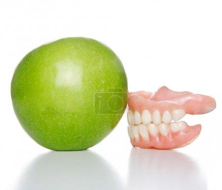 False teeth denture against green granny smith app...