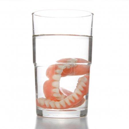 False teeth having a swim in transparent water gla...