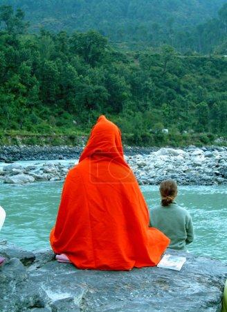 Photo for Orange swami monk meditating on rock on the bank of ganges - Royalty Free Image
