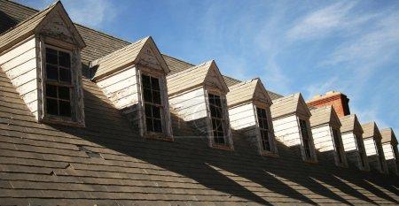 Photo pour Un toit de bardeaux et de neuf lucarnes ayant besoin de réparation - image libre de droit