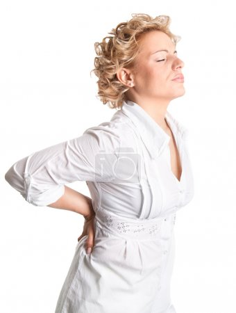 Young woman holds her back in pain.