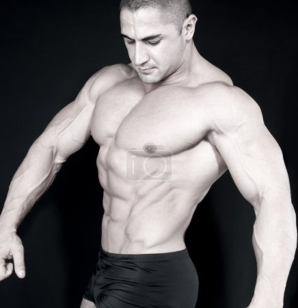 Athletic sexy attractive male body builder, demonstrating contest pose
