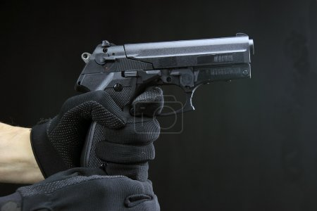 Shooting Handgun against black background...