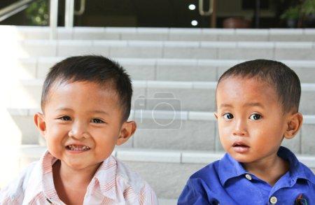 Foto de Dos niños pequeños que tienen diferente expresión en el exterior - Imagen libre de derechos