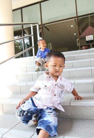 Foto de Twee kleine kinderen die op de trappen in buiten spelen - Imagen libre de derechos