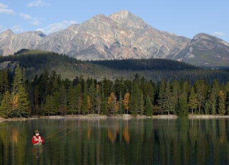 Photo pour Jeune homme pataugeant dans le lac pêche à la mouche avec de belles montagnes en arrière-plan . - image libre de droit