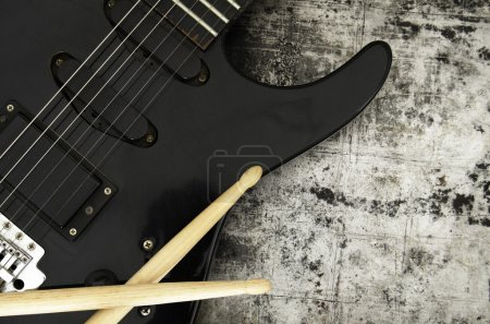 Photo for Electric guitar and drumsticks on a grunge background - Royalty Free Image
