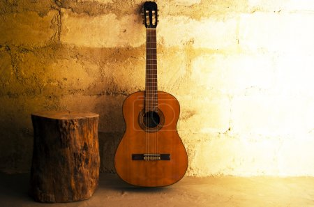 Photo for Acoustic guitar on old wall and stump - Royalty Free Image