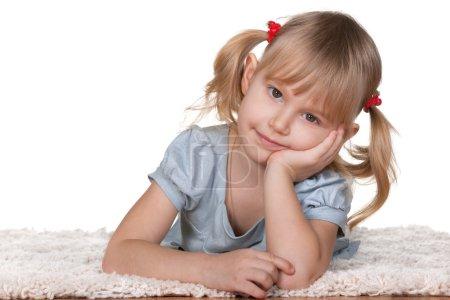 Fille réfléchie couchée sur le tapis épais