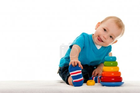 Photo for A little boy is playing with toys on the blanket; isolated on the white background - Royalty Free Image