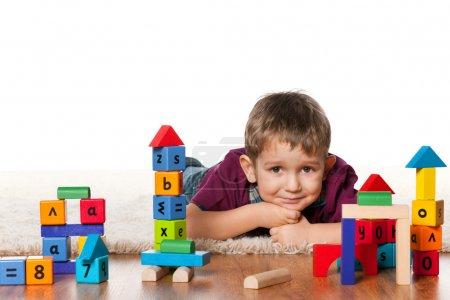 Little boy on the floor near toys