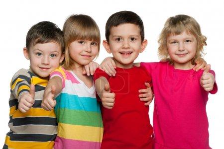 Photo pour Quatre enfants se tiennent ensemble ; isolés sur le fond blanc - image libre de droit