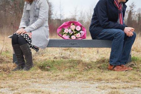 Photo pour Couple avec difficultés, assis sur un banc avec bouquet entre les deux - image libre de droit