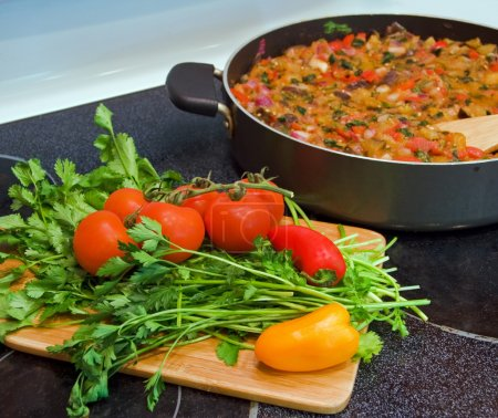 Photo for Stove top with vegetable stew in frying pan and cutting board with vegetables and herbs - Royalty Free Image