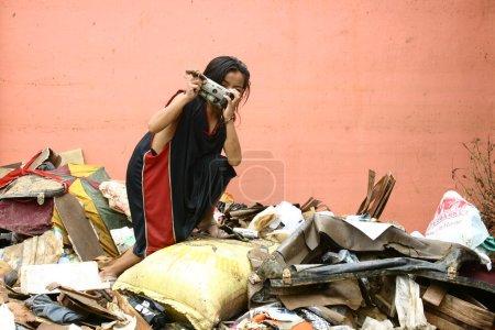 Foto de Una foto de una chica carroñero que encontró una cámara rota en una pila o escombros. - Imagen libre de derechos