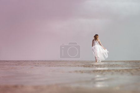 Photo for Beautiful woman walking on the sea shore wearing white dress - Royalty Free Image