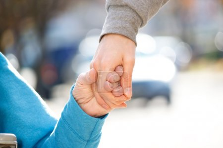 Photo for Young Caregiver Holding Senior's Hand Outside - Royalty Free Image
