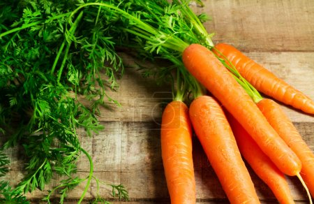 Photo for Fresh carrots bunch on wood - Royalty Free Image