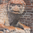 Sculpture of a lion holding a snake with legs - an...