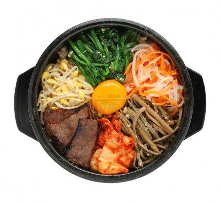 Photo pour Bibimbap dans un bol en pierre chauffée, plat coréen sur fond blanc - image libre de droit