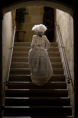 Photo for Victorian lady in castle stairs. 1900 Style. - Royalty Free Image