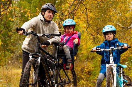 Happy active family cycling on bikes outdoors