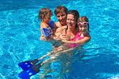 Happy active family with kids in swimming pool