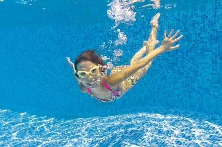 Happy child swims underwater in swimming pool