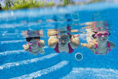 Underwater smiling family having fun and playing in swimming pool