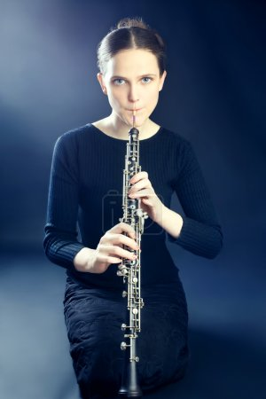 Young musician playing oboe musical instrument