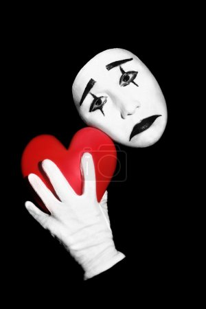 Photo for Mime with red heart. Actor mime with black and white make-up holding red heart in the hand. Isolated on black background. - Royalty Free Image