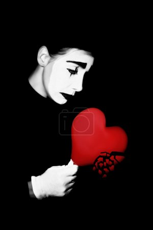 Photo for Melancholic actor mime in dramatic black and white make-up with broken heart. - Royalty Free Image