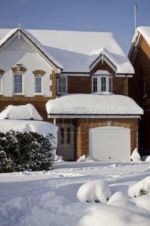 Photo pour Une maison couverte de neige très belle et pittoresque. tourné sous la lumière naturelle du soleil avec espace copie fournie au bas. - image libre de droit