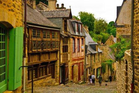 Photo pour Rue médiévale pavée menant au port par la rivière Rance avec des maisons en pierre et en bois de style architectural breton dans le vieux quartier de Dinan, Bretagne, France - image libre de droit