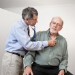 Male doctor listening to older man's heart with st...