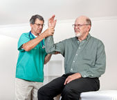 Doctor Examines Patient's Wincing with Pain in Arm