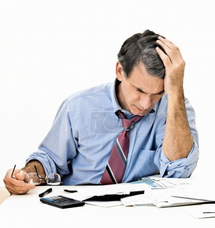Photo for Man at desk in shirt and tie holding his head and worrying about money. - Royalty Free Image