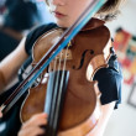 Постер, плакат: Young Woman Playing Violin Closeup