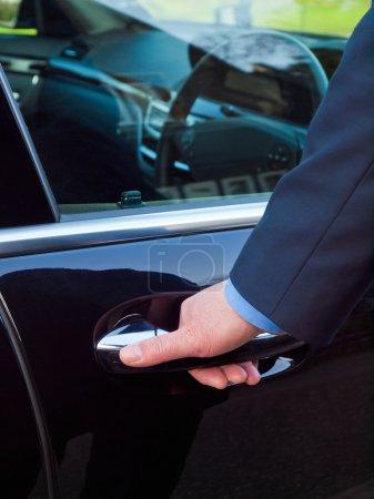Photo pour La main d'un homme d'affaires ouvrant la porte de sa voiture de luxe - image libre de droit
