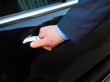 Photo for Chauffeur's hand opening passenger door on a black limousine - Royalty Free Image