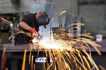 Photo pour Sparks friture sur la table de travail pendant le broyage du métal - image libre de droit