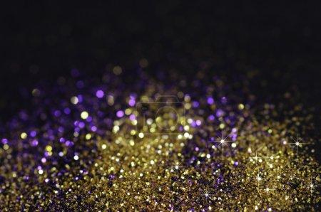 Photo pour Paillettes or et violet sur fond noir avec mise au point sélective - image libre de droit