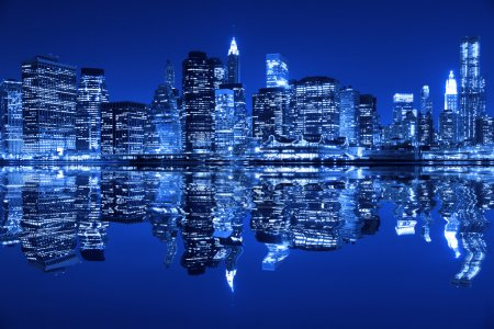 Photo for Lower Manhattan in New York City at night with reflection in water with blue hue - Royalty Free Image