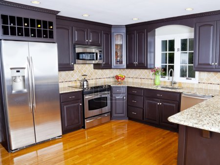 Photo for Modern domestic kitchen with new appliances and wooden floor - Royalty Free Image