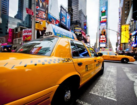 Photo pour NEW YORK - DECEMBER 17: Yellow cab speeds through Times Square the busy tourist intersection of neon art and commerce and is an iconic street of New York City - image libre de droit